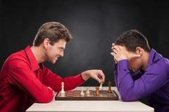 Freunde, die Schach auf schwarzem Hintergrund spielen Stockfoto