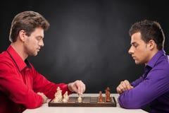 Freunde, die Schach auf schwarzem Hintergrund spielen Stockbilder