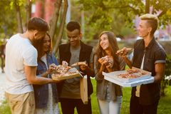 Freunde, die Scheiben der Pizza teilen stockfotos