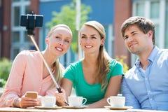 Freunde, die Selfie mit Selfie-Stock nehmen Lizenzfreies Stockbild