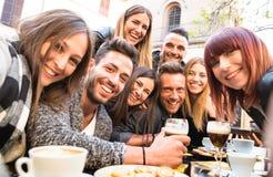 Freunde, die selfie an trinkendem Cappuccino des Barrestaurants nehmen und stockbild