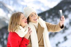 Freunde, die selfies in einem schneebedeckten Berg nehmen lizenzfreies stockfoto