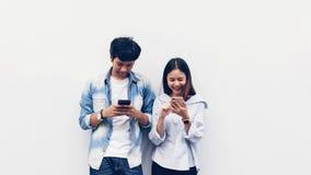 Freunde, die Smartphone, w?hrend der Freizeit verwenden Das Konzept der Anwendung des Telefons ist im Alltagsleben wesentlich lizenzfreies stockbild
