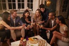Freunde, die Snäcke essen, wie sie an der Partei zusammen feiern lizenzfreie stockbilder