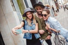 Freunde, die Spaß beim Nehmen von selfie auf einem Bürgersteig haben stockfotografie