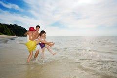 Freunde, die Spaß durch den Strand haben Lizenzfreie Stockfotos