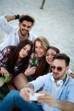 Freunde, die Spa? auf Strand am Sommer partying und gehabt worden sein w?rden stockfotos