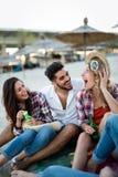 Freunde, die Spa? auf Strand am Sommer partying und gehabt worden sein w?rden lizenzfreie stockbilder