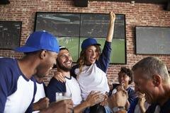 Freunde, die Spiel im Sportbar auf den feiernden Schirmen aufpassen lizenzfreies stockfoto