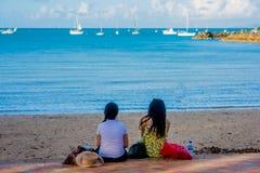 Freunde, die am Strand sich entspannen Stockbild