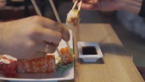 Freunde, die Sushi und Bad in der Soße im Sushi-Bar essen stock video