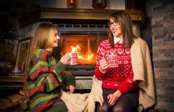 Freunde, die Tee trinken und durch den Kamin genießen stockbilder