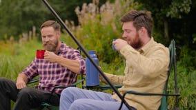 Freunde, die Tee von der Thermosflasche fischen und trinken stock footage