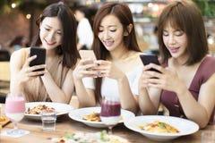 Freunde, die Telefon des Abendessens und des Aufpassens intelligentes im Restaurant haben stockfotografie