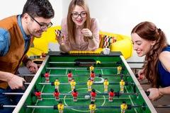 Freunde, die Tischfußball spielen Stockfoto