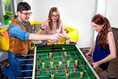 Freunde, die Tischfußball spielen Stockfotos