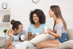Freunde, die, trinkender Kaffee heraus zu Hause lachen sprengen lizenzfreie stockfotografie