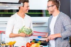 Freunde, die vegies und Fleisch in der inländischen Küche kochen Lizenzfreies Stockfoto
