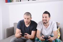 Freunde, die Videospiele auf Couch spielen lizenzfreie stockbilder