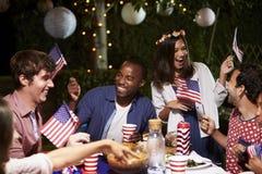 Freunde, die 4. von Juli-Feiertag mit Hinterhof-Partei feiern Stockbilder