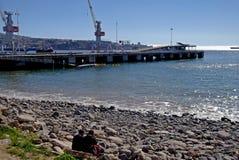 Freunde, die vor dem Meer im chilenischen Hafen sitzen Stockfotografie