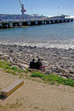 Freunde, die vor dem Meer im chilenischen Hafen sitzen Lizenzfreie Stockbilder