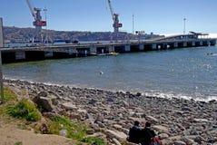 Freunde, die vor dem Meer im chilenischen Hafen sitzen Stockfotos