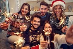 Freunde, die Weihnachten mit Wunderkerzen feiern Lizenzfreie Stockfotos
