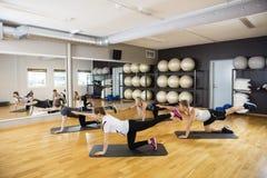 Freunde, die Yoga in der Turnhalle durchführen lizenzfreies stockbild