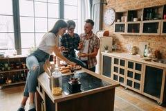 Freunde, die zu Abend essen und Pizza an der Küche teilen stockbilder