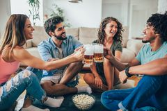 Freunde, die zu Hause Popcorn essen und Bierkrug, Spaß habend trinken lizenzfreies stockbild