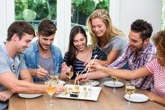 Freunde, die zu Hause Wein und Sushi genießen Lizenzfreies Stockfoto