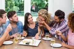 Freunde, die zu Hause Wein und Sushi genießen Stockbild