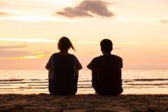 Freunde, die zusammen auf dem Strand sitzen Stockbild