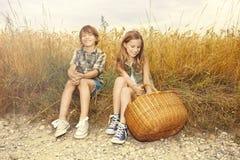 Freunde, die zusammen auf einem Gebiet des Weizens picknicken stockfotografie