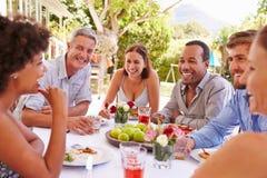 Freunde, die zusammen an einem Tisch in einem Garten speisen stockfotografie