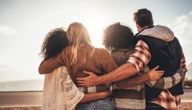 Freunde, die zusammen stehen und das Meer betrachten lizenzfreies stockfoto