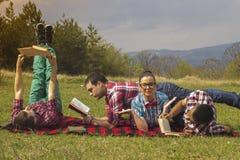 Freunde draußen mit Buch stockfotos