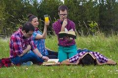 Freunde draußen mit Buch lizenzfreie stockfotografie