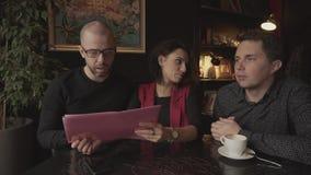 Freunde in einer Caféunterhaltung Mädchen zeigt Männer in Ihrem Projekt im rosa Ordner stock footage