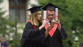 Freunde graduiert die tragenden akademischen Kleider, die Fotos auf Smartphone ansehen stock video