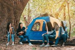 Freunde gruppieren von den jungen Asiatinnen, die am Wald kampieren und stillstehen stockfotos