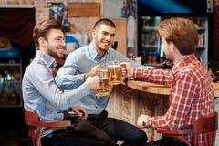 Freunde haben ein Bier an der Kneipe Stockbild