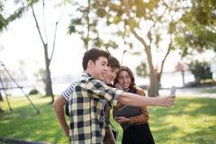 Freunde im Park, der unter Verwendung Smartphonesvideoanruf selfie schaut stockfotos