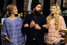 Freunde im Shop: Damen und Herr in den teuren Mänteln stockbilder