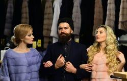 Freunde im Shop: Damen und Herr in den teuren Mänteln lizenzfreies stockfoto