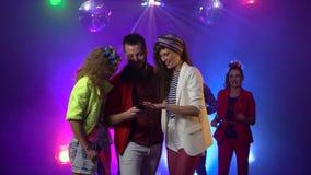 Freunde im Verein betrachten etwas am Telefon um Leute tanzen in den Rauch Rauchen Sie Hintergrund stock footage
