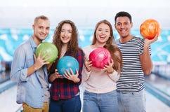 Freunde mit Bowlingkugeln Lizenzfreies Stockfoto