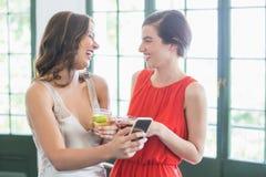 Freunde mit Cocktailgläsern lachend bei der Anwendung des Handys Lizenzfreie Stockfotos