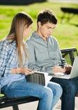Freunde mit dem Laptop und Buch, die im Campus sitzen stockbild